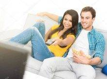 Young Happy Interracial Couple Watching Tv On The Couch